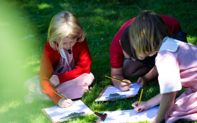 pupils writing in grass